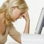 Frustrated Woman at Computer With Stack of Paper --- Image by © Royalty-Free/Corbis
